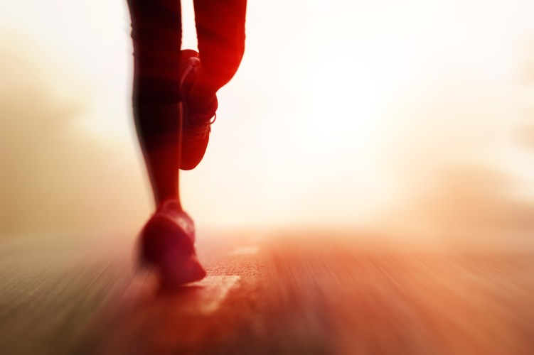 Runner athlete feet running on road. woman fitness silhouette sunrise jog workout welness concept. with motion blur