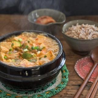 Doenjang jjigae (Korean stew) is boiling in a stone pot