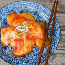Korean traditional radish kimchi served on a blue plate and chopsticks