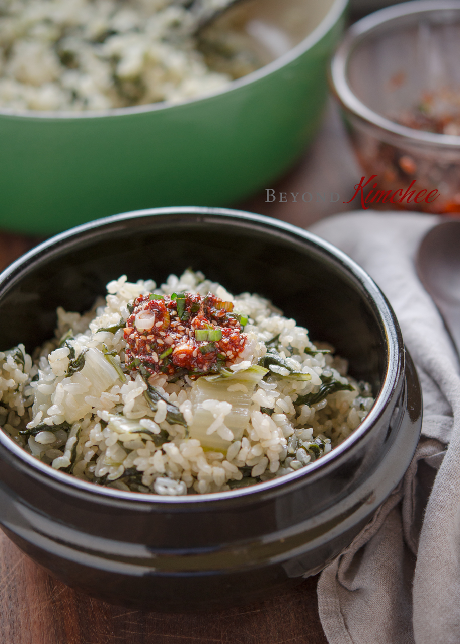 Swiss chard with brown rice is topped with chili sauce in a stone pot