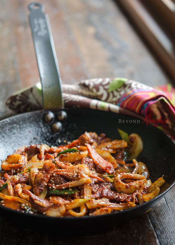 Pork belly and squid are stir-fried in a spicy sauce made with Korean chili paste and curry powder.