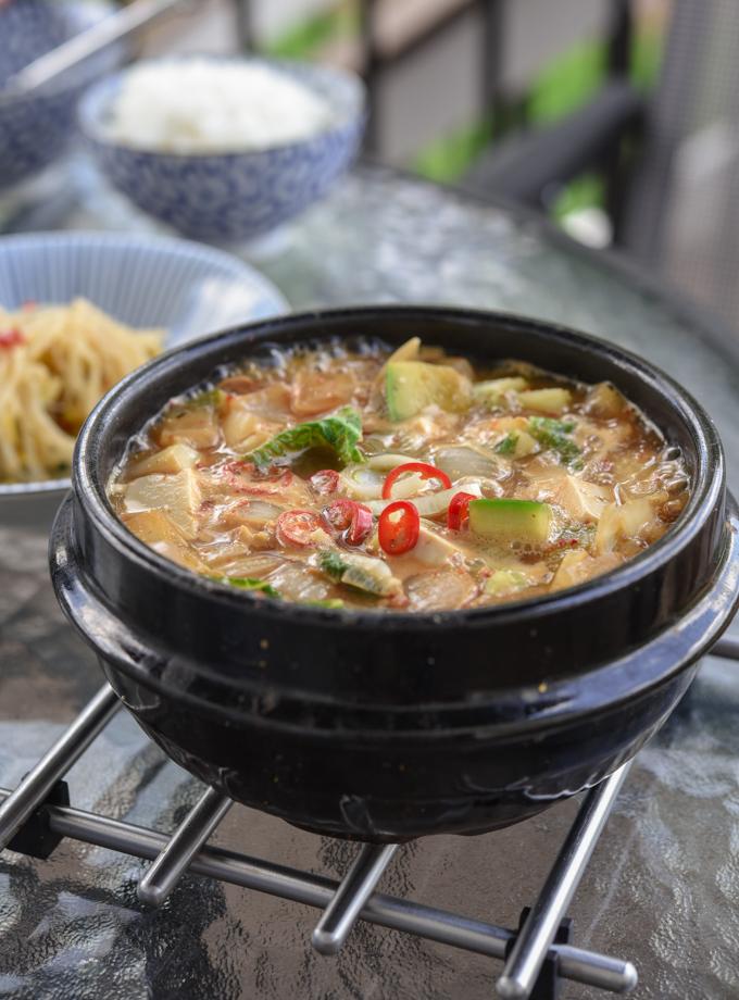 Korean doenjang jjigae is boiling up in a stone pot