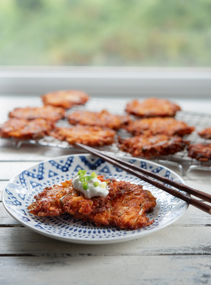 Cheesy Kimchi Potato Pancakes are garnished with a dollop of sour cream.