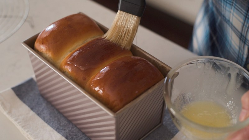 brushing with melted butter gives milk bread a shiny look