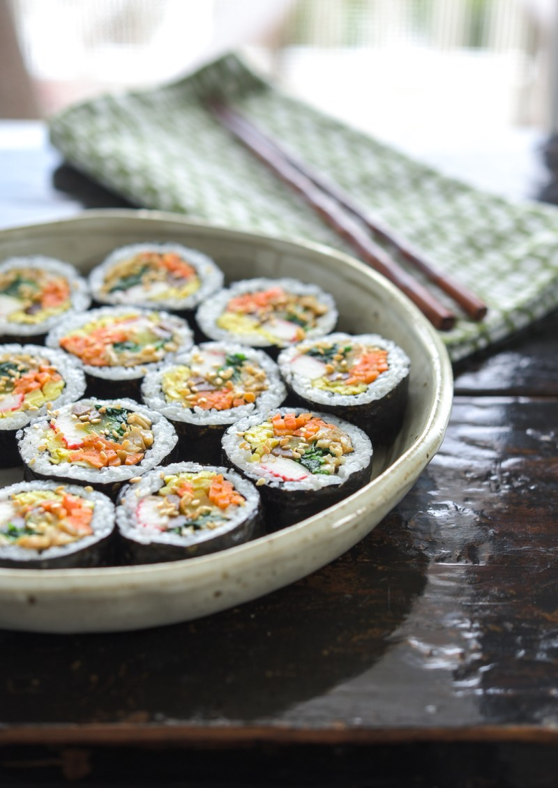 Kimbap pieces are garnished with toasted sesame seeds