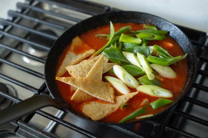 White rice cakes are added to the anchovy and gochujang stock in a skillet to make Tteokbokki.