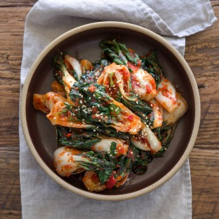 Bok choy kimchi made with fresh chili shows its vibrant red color in a bowl.