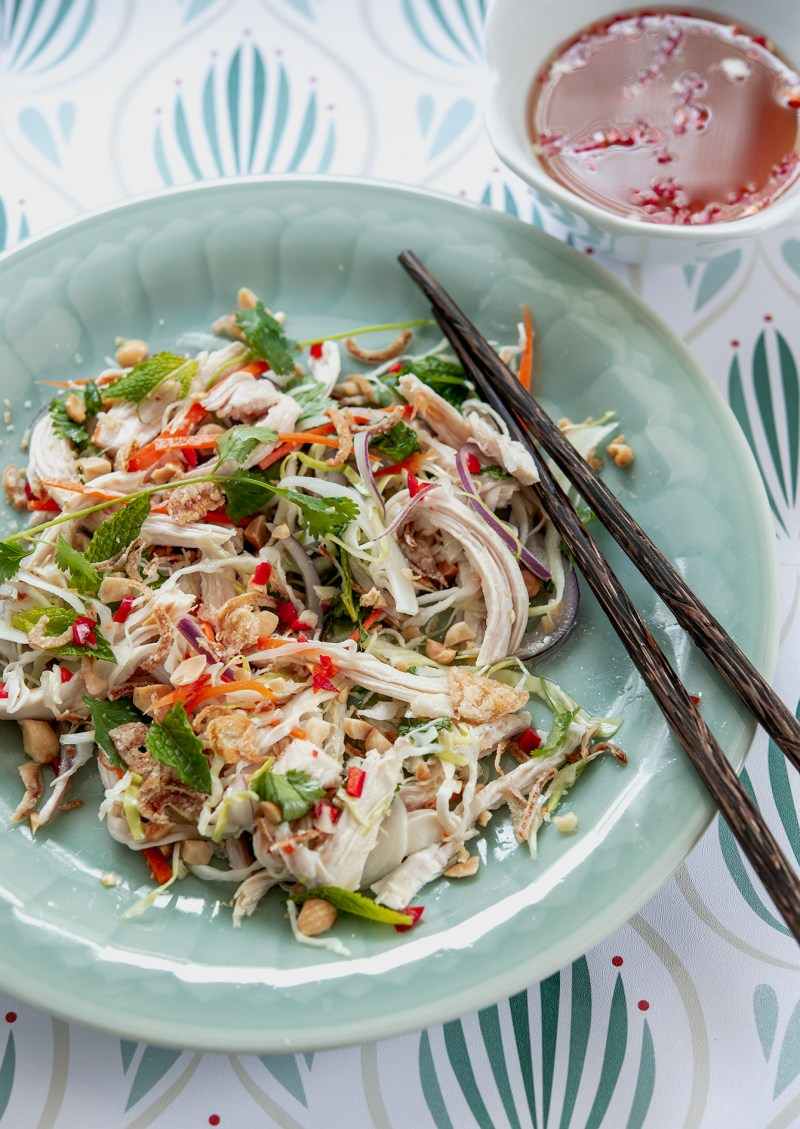 Yummy Vietnamese chicken salad is served on a green plate with fish sauce dressing.