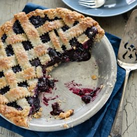 Maple blueberry pie with lattice top crust is cut and served