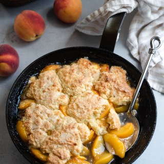 Southern classic peach cobbler with biscuit topping baked in a cast iron skillet
