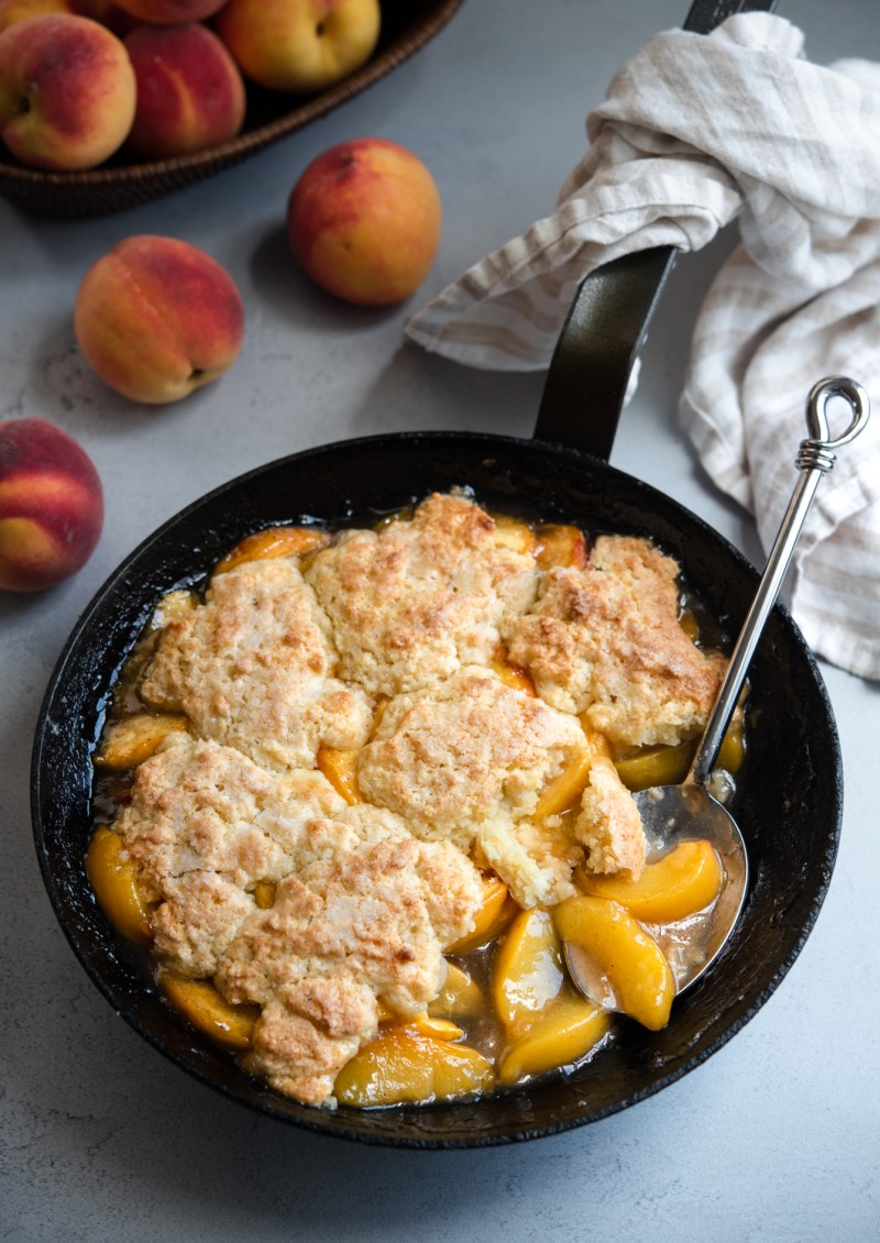 Southern classic peach cobbler with biscuit topping baked in a cast iron skillet.