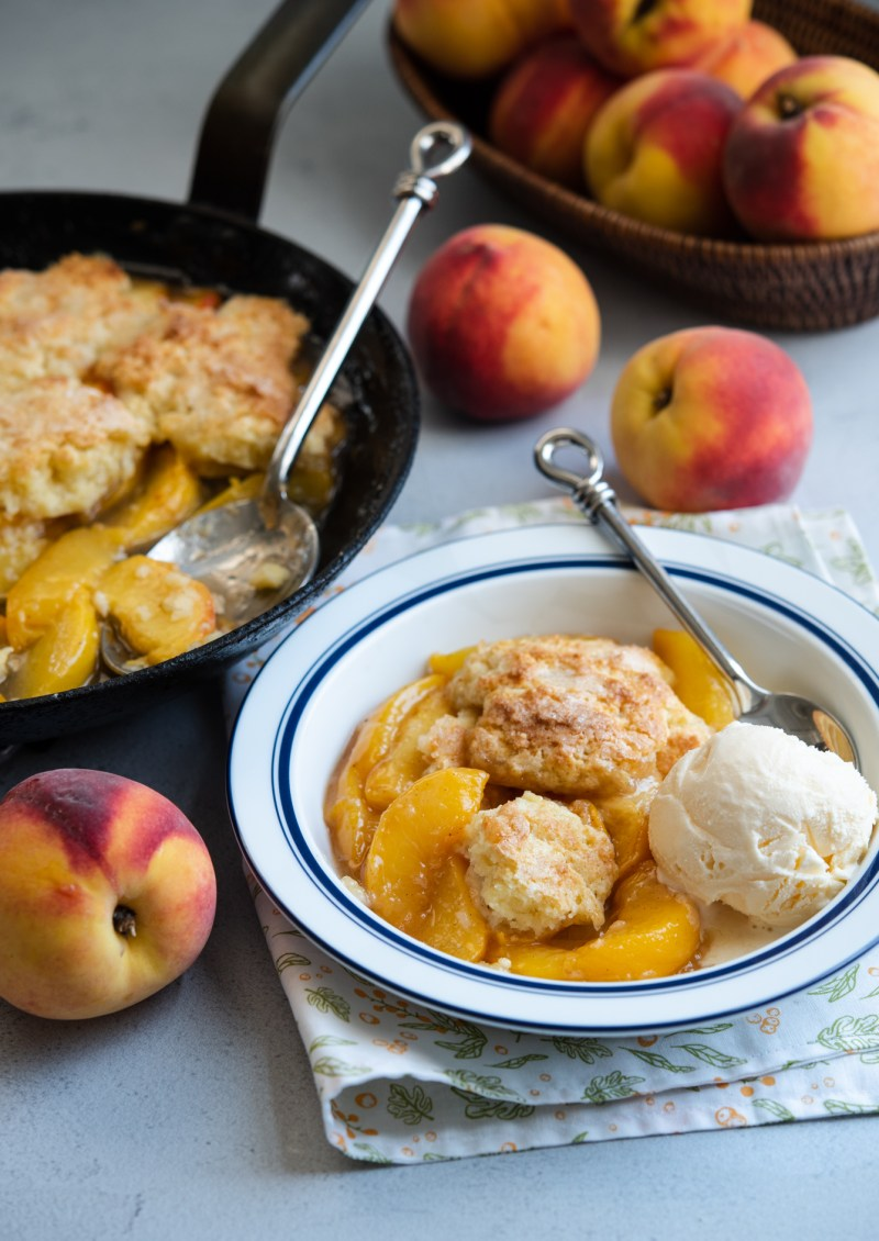 biscuit topped peach cobbler is served with vanilla ice cream.