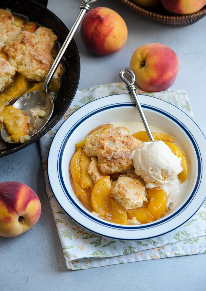Old fashioned peach cobbler with biscuit topping is served with vanilla ice cream.