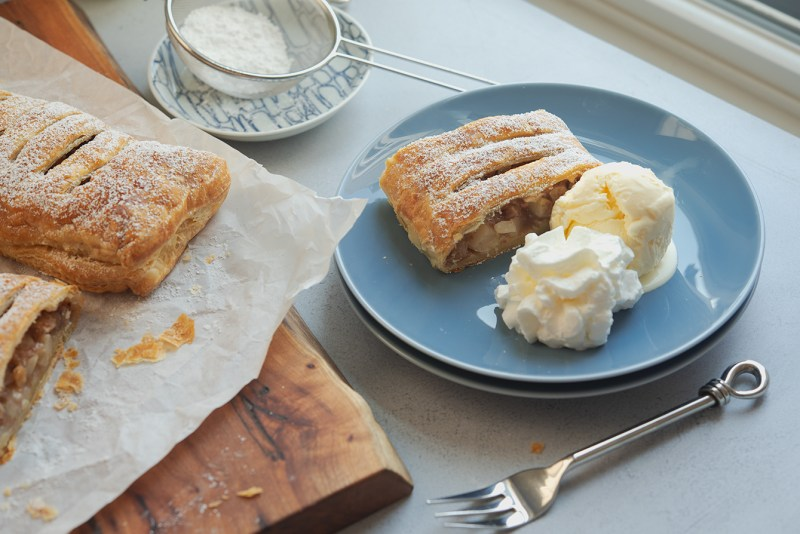 A slice of apple strudel is sesrved with vanilla ice cream and whipped cream on a blue plate.