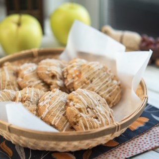Soft apple cookies are served in a lined basket with apples behind.