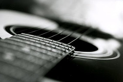 Photograph of a guitar, with strings, in black and white and with depth of field.