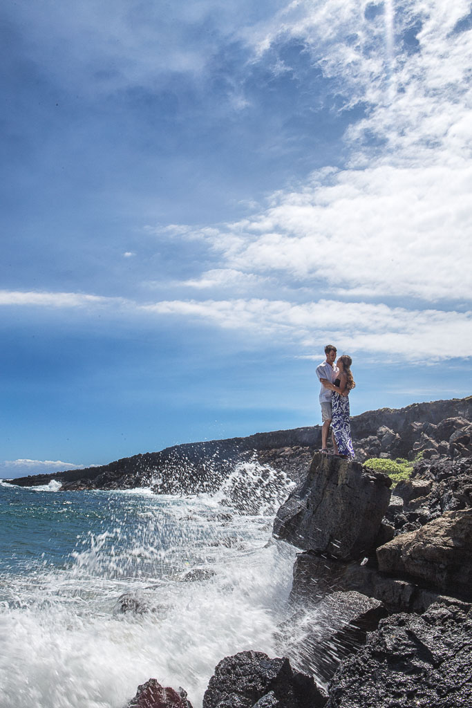 Hawaii Portrait engagement photo green sand beach couple on rocks with crashing waves
