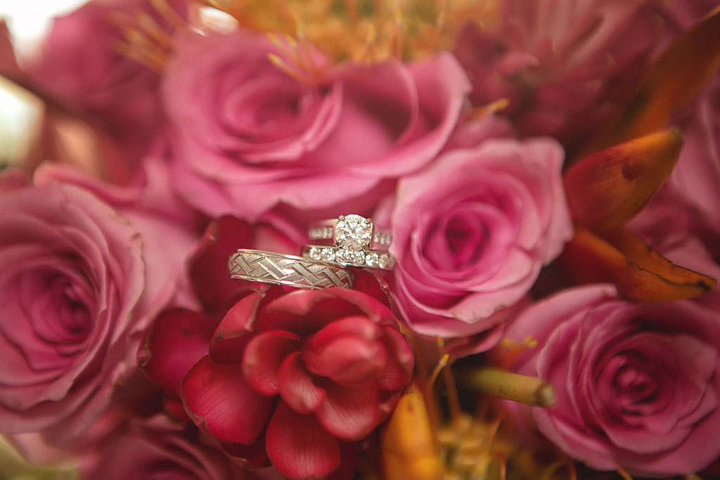 Hawaii wedding professional photographer wedding rings in rose bouquet
