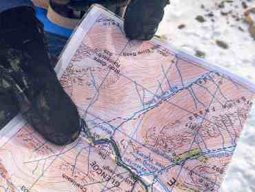 A gloved hand holding a map whilst on a navigation course.