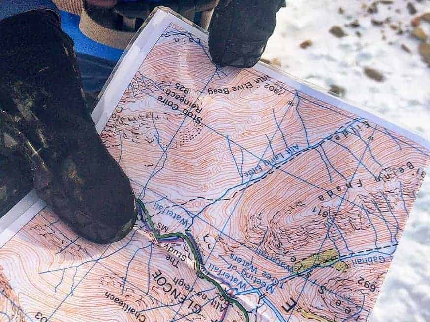 A gloved hand holding a map on a navigation course