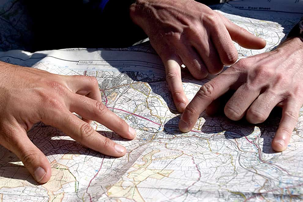 Sets of hands on a map whilst learning to navigate