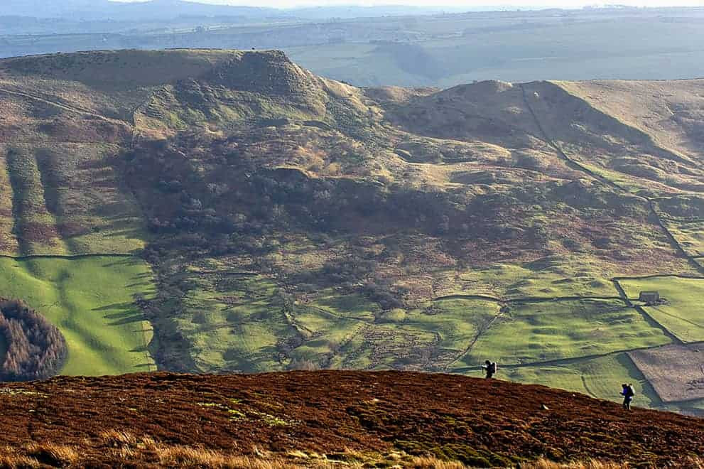 Two people navigating on Edale moor with Mam Tor in the background on a Peak District navigation course.