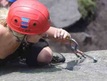 A lady learning to lead climb on a rock climbing course in the Peak District