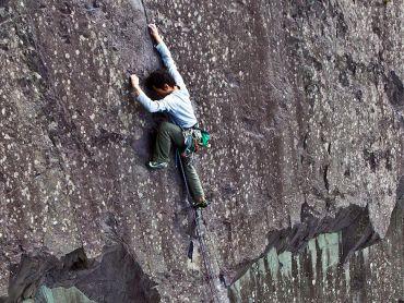 A man rock climbing in the Peak District
