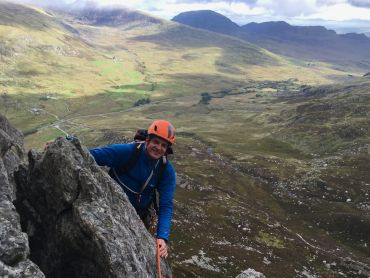 A man scrambling on the East face of Tryfan in Snowdonia.