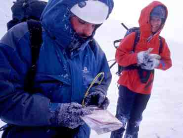 Intermediate navigation by two people with map and compass in snow