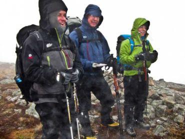 3 men stood on a mountain