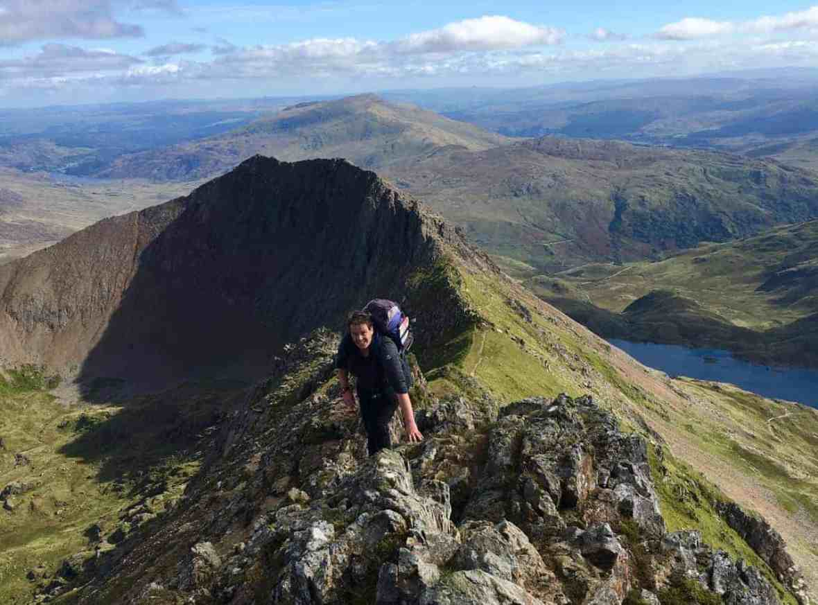 A lady scrambling along the upper slopes of Crib Coch after completing the classic Grade 1 scramble.