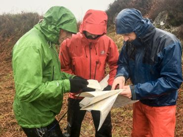 3 men study their maps whilst teaching navigation on the hills in the Peak District