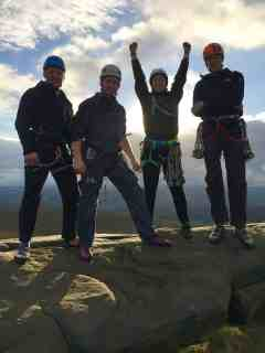 Four people at the top of a rock climb equals Peak District team building success