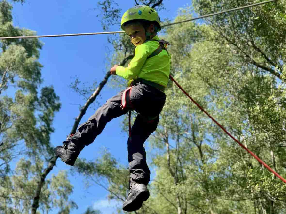 A child on a zip line on a Peak District family adventure day