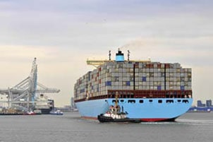 Ocean Freight Forwarder-Tug boat pulling a full container ship into dock.