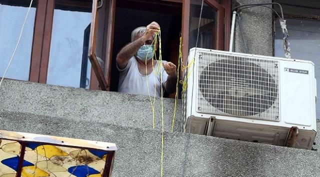 एक कोरोना मरीज खिड़की के रास्ते रस्सी से जरूरत का सामान लेते हुए.