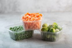 Frozen vegetables such as green peas, brussels sprouts and baby carrot in the plastic boxes