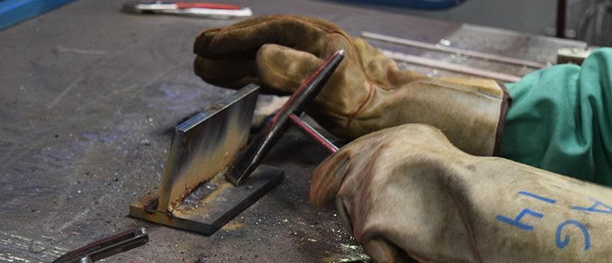 Welding student hammering