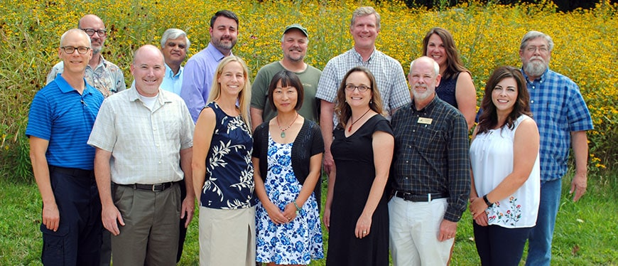 Professors and Instructors stand in front of flower