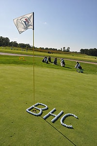 Black Hawk College initials spelled in golf balls on the green