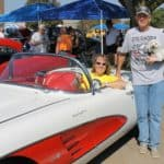 Bettie Truitt sitting in white & orange Corvette, Ron Williams standing next to car holding white dog