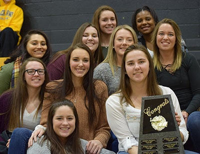 Softball team with the academic award sitting in the bleachers