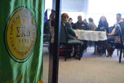 Sigma Kappa Delta green banner with students seated in background