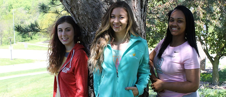 Three female students standing outside in Black Hawk College gear