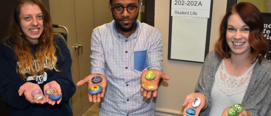 three students holding painted kindness rocks