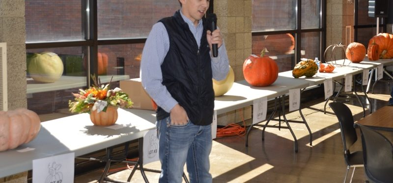 Male student with microphone talking in front of tables with pumpkins