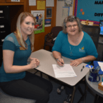 Disability Services employees Alisa Kotaska and Susan Sacco sit at a table