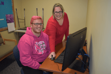 Black Hawk College student sits at a desk while Disability Services employee uses a computer