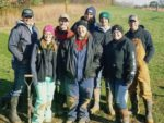 8 men and women wearing winter clothing standing in a grassy field